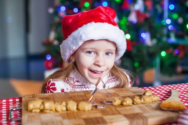 Biscotti divertenti del pan di zenzero di natale di cottura della bambina