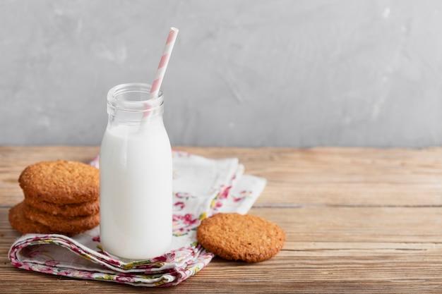 Biscotti e bottiglia per il latte dell'angolo alto con paglia sulla tavola