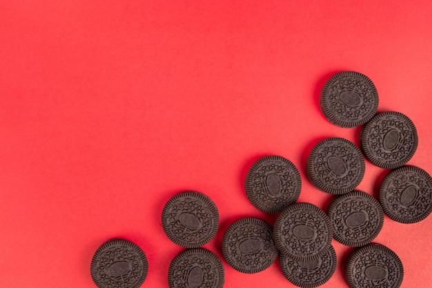 Biscotti e crema di roba alla vaniglia in pezzi impilati in gruppo su sfondo rosso per christm