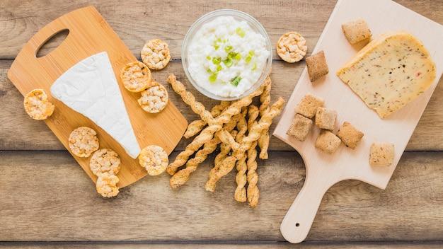 Biscotti e grissini del formaggio con formaggio in ciotola sul contesto di legno