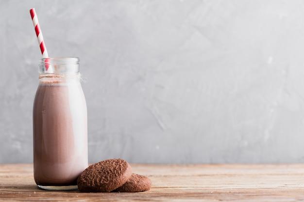 Biscotti e latte al cioccolato di vista frontale in bottiglia con paglia sulla tavola