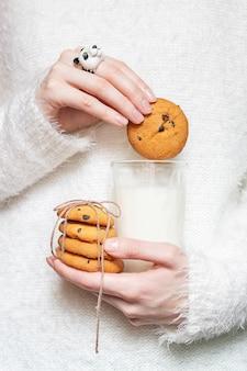 Biscotti e latte nelle mani