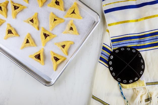 Biscotti ebraici crudi sulla teglia da forno con kippa e tallit