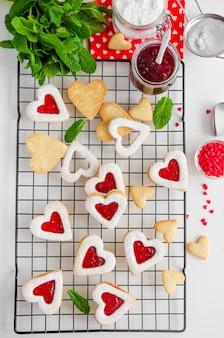 Biscotti fatti in casa a forma di cuore con marmellata di bacche e zucchero a velo su una griglia metallica con foglie di menta