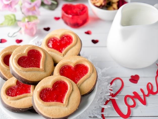 Biscotti fatti in casa con un cuore di marmellata rossa san valentino