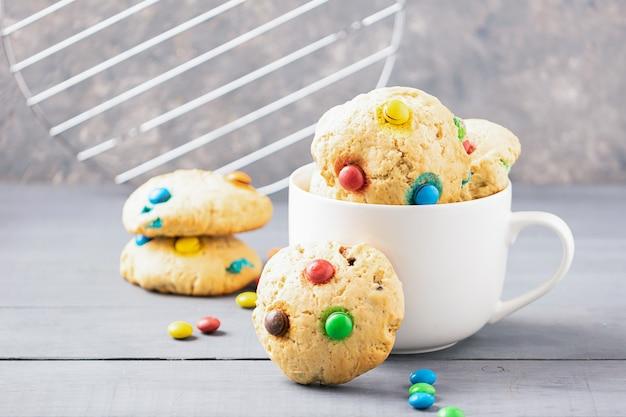 Biscotti fatti in casa decorati con caramelle colorate jelly bean in una tazza bianca