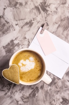 Biscotti fatti in casa di pan di zenzero a forma di un cuore su una tazza di cappuccino