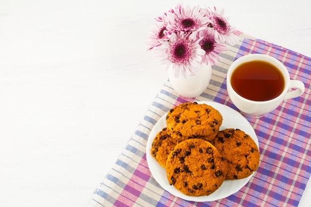 Biscotti fatti in casa e tazza di tè sul tovagliolo a scacchi