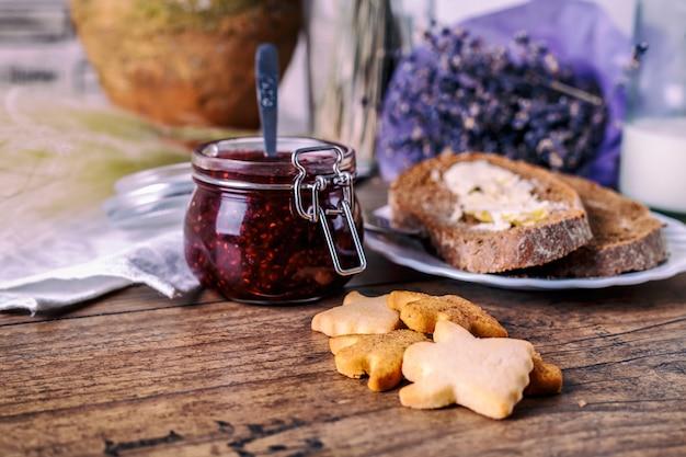 Biscotti fatti in casa miele miele, marmellata di lamponi in barattolo, pane e burro, coltello, su un fondo di legno. concetto di colazione.