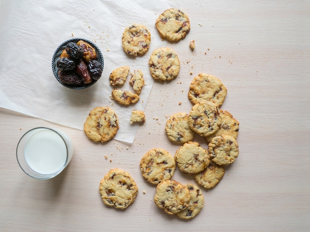 Biscotti freschi della data succosa con latte su una superficie di legno leggera