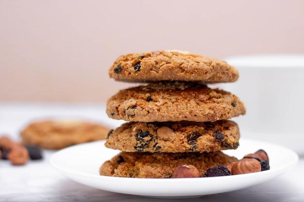 Biscotti friabili della farina d'avena fresca su un piatto con le noci e l'uva passa. il concetto di una colazione deliziosa e salutare.