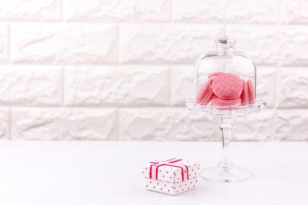 Biscotti macaron rosa in un vaso di cristallo e una confezione regalo