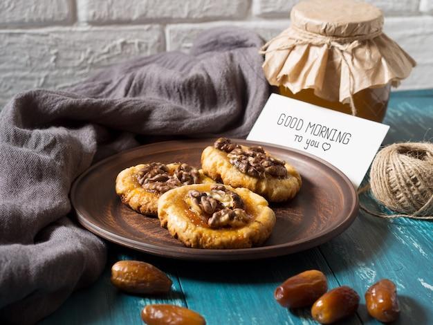 Biscotti, miele e date con una carta bianca per l'iscrizione.