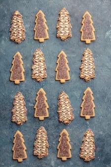 Biscotti pan di zenzero di natale a forma di un albero di natale su sfondo blu