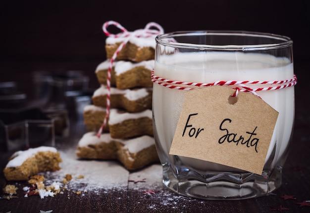 Biscotti per santa con bicchiere di latte con etichetta per babbo natale e albero di natale