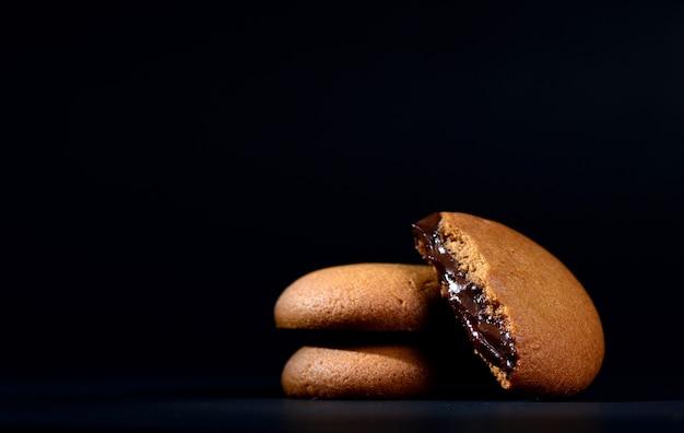 Biscotti ripieni di crema al cioccolato. biscotti alla crema di cioccolato. biscotti al cioccolato fondente ripieni di crema.