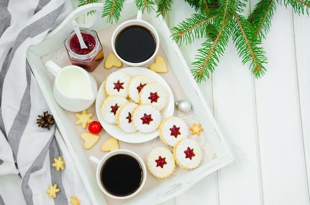 Biscotti ripieni di marmellata di fragole su un vassoio con due tazze di caffè