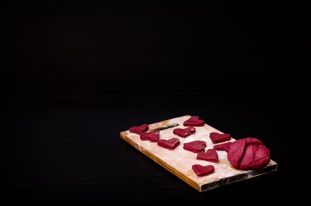 Biscotti rossi a forma di cuore su una tavola di legno, cuocendo il giorno di san valentino