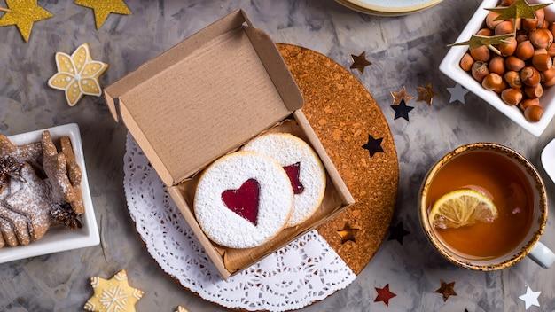 Biscotti rotondi con marmellata a forma di cuore in confezione regalo tra decorazioni natalizie