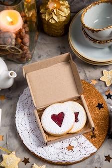 Biscotti rotondi con marmellata a forma di cuore in confezione regalo tra le decorazioni natalizie
