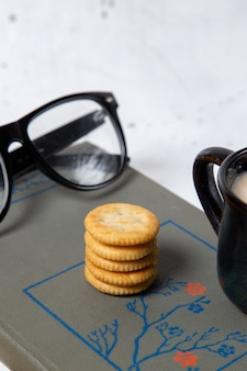 Biscotti rotondi di vista frontale con gli occhiali da sole e la tazza di latte sullo spuntino croccante del cracker del biscotto bianco