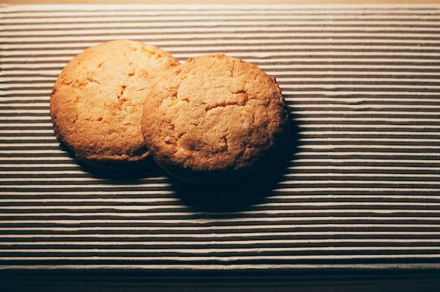 Biscotti rotondi, su fondo strutturato del cartone, progettazione semplice, spazio della copia