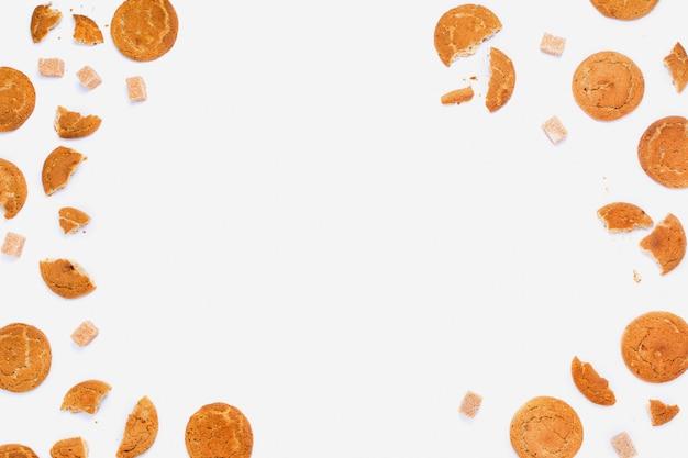 Biscotti rotti e cubetti di zucchero di canna su bianco, copyspace, disposizione del telaio flatlay