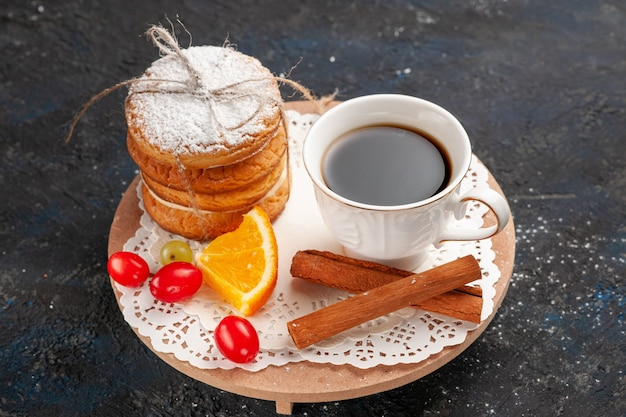 Biscotti sandwich vista ravvicinata con ripieno di crema insieme a cannella e caffè sul biscotto con superficie scura