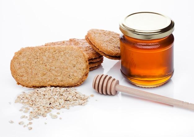 Biscotti sani del chicco di prima colazione della prima colazione con miele e porridge crudo dell'avena su fondo bianco