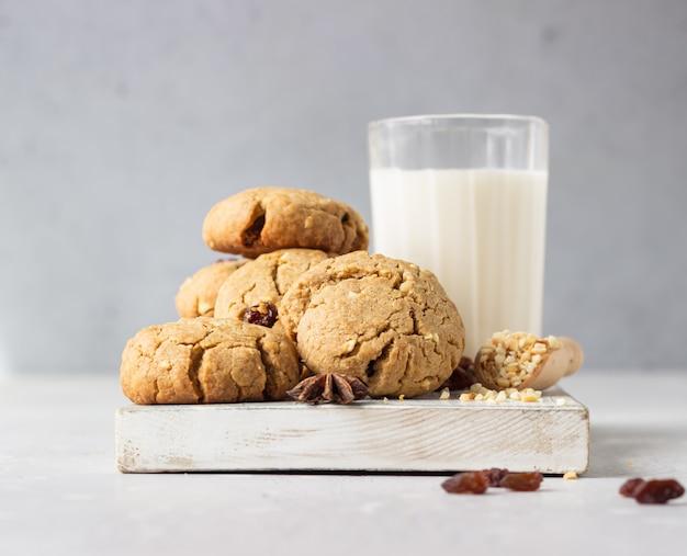 Biscotti sani del grano saraceno con l'uva passa e le noci con un bicchiere di latte