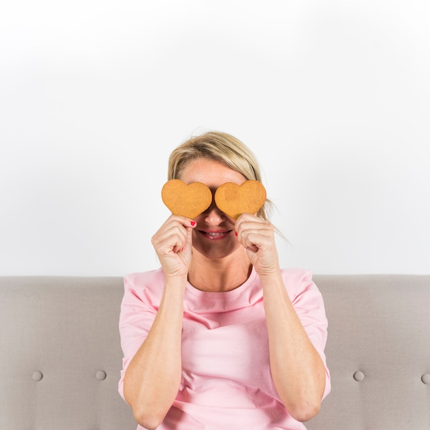 Biscotti sorridenti di forma del cuore della tenuta della donna lei occhi contro il contesto bianco