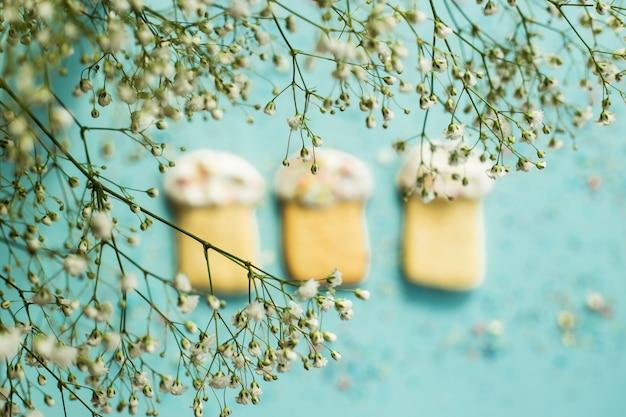 Biscotti sotto forma di dolci pasquali su uno sfondo blu tra i fiori di gypsophila