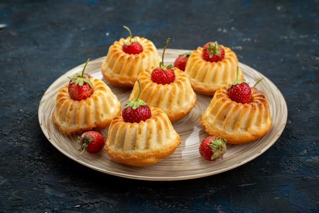 Biscotti squisiti di vista frontale con fragole rosse all'interno del piatto bianco sullo scrittorio scuro