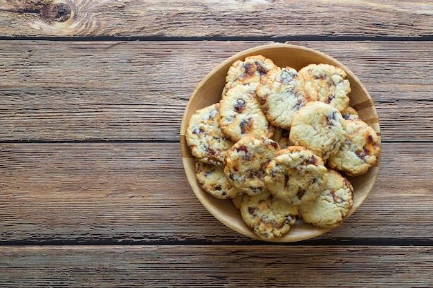 Biscotti succosi freschi della data in una ciotola su una superficie di legno marrone.