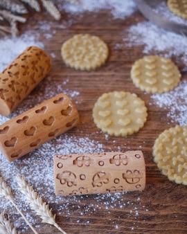 Biscotti timbrati con una stampa di cuori e farfalle. mattarelle in legno per biscotti
