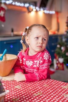 Biscotti tristi del pan di zenzero di natale di cottura della bambina triste