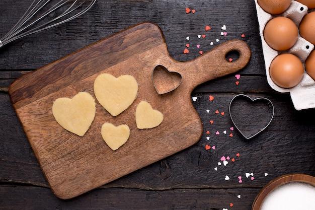 Biscotti, utensili da cucina e cuori su legno