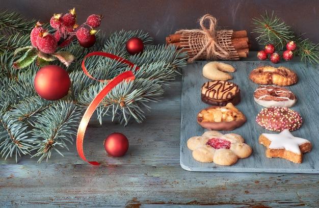 Biscotti vari con bastoncini di cannella, ramoscelli di albero di natale, palline e bacche