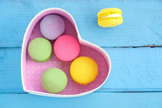 Biscotti variopinti del macaron e una scatola in forma di cuore su un fondo d'annata di legno blu