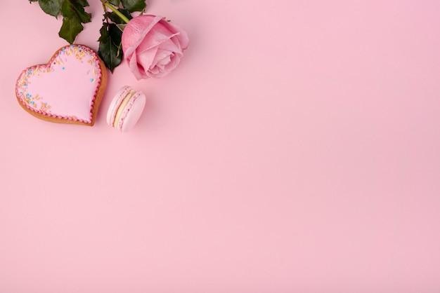 Biscotto a forma di cuore con rosa e macaron