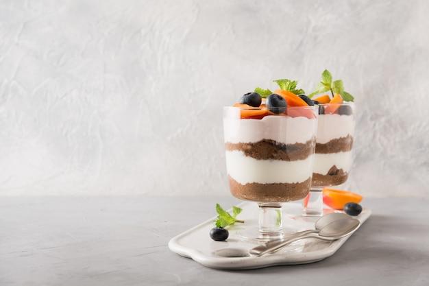Biscotto al cioccolato a strati dessert con bacche fresche e delicata crema di formaggio su grigio.