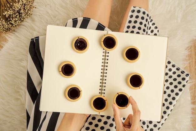 Biscotto al cioccolato nella mano di una signora a pois e abito a righe sul libro vuoto con biscotti al cioccolato disposti a forma di cerchio seduto sul tappeto di pelliccia bianca soffice