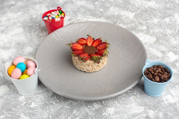 Biscotto con fragole e cioccolato rotondo all'interno del piatto viola insieme a semi di caffè e caramelle