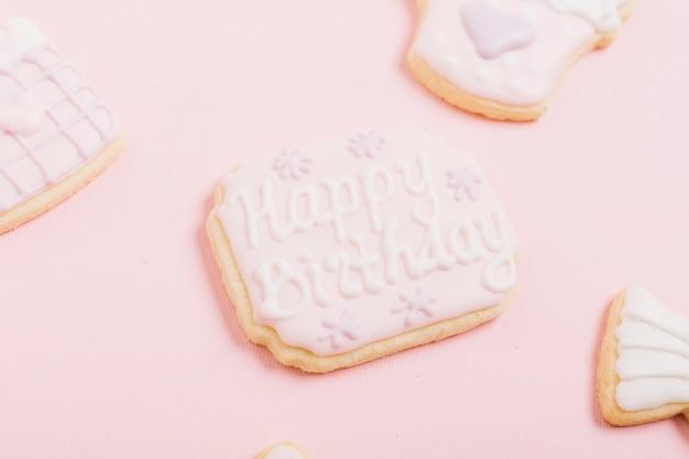 Biscotto cremoso fresco con il testo di buon compleanno sopra fondo bianco