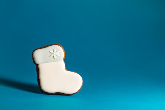 Biscotto del pan di zenzero della scarpa bianca di santa sul blu