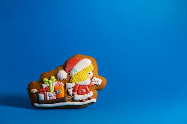 Biscotto del pan di zenzero di piccolo postino sveglio di santa su copyspace blu