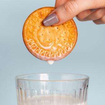 Biscotto tenuto sopra il primo piano del bicchiere di latte