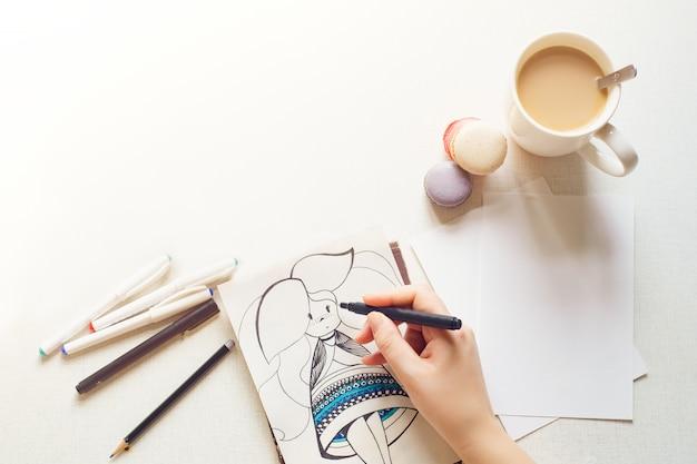Biškek, kirghizistan - 17 febbraio 2018: concetto di pittura. l'artista disegna una ragazza che beve una tazza di caffè.