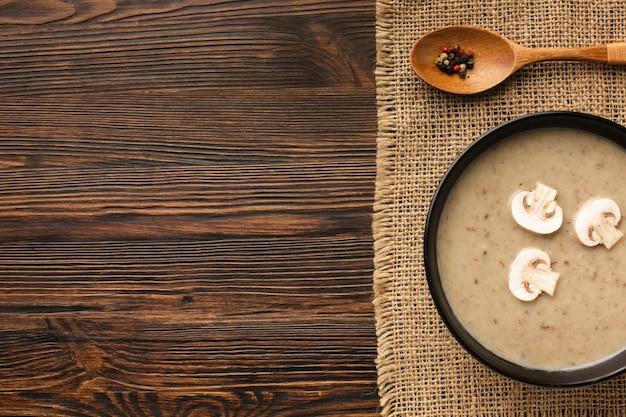 Bisque e cucchiaio dei funghi di disposizione piana con lo spazio della copia