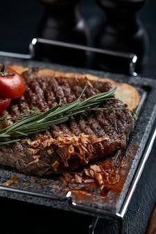 Bistecca alla griglia con coltello e forchetta scolpiti su pietra ardesia nera.